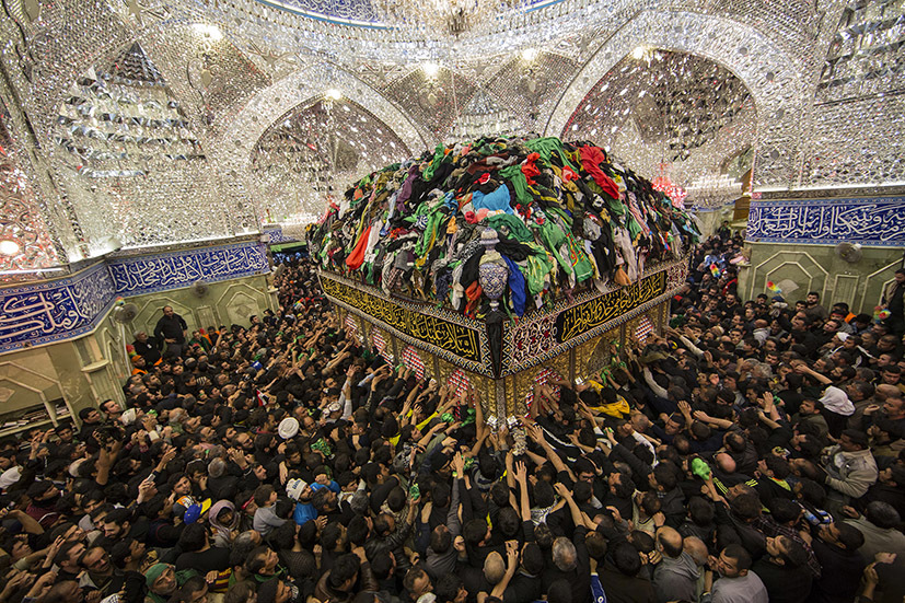 Shi'ite Muslim pilgrims reach out to touch the tomb of Imam al-Abbas located inside the Imam al-Abbas shrine to mark Arbain in the holy city of Kerbala